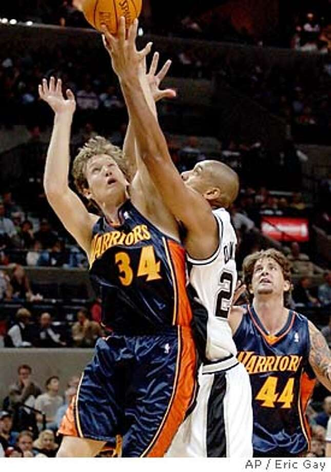 Golden State Warriors forward Mike Dunleavy (34) battles San Antonio Spurs forward Tim Duncan (21) for a rebound in the first quarter in San Antonio, Tuesday, Nov. 18, 2003. Warriors forward Cherokee Parks (44) helps defend on the play. (AP Photo/Eric Gay) Photo: ERIC GAY