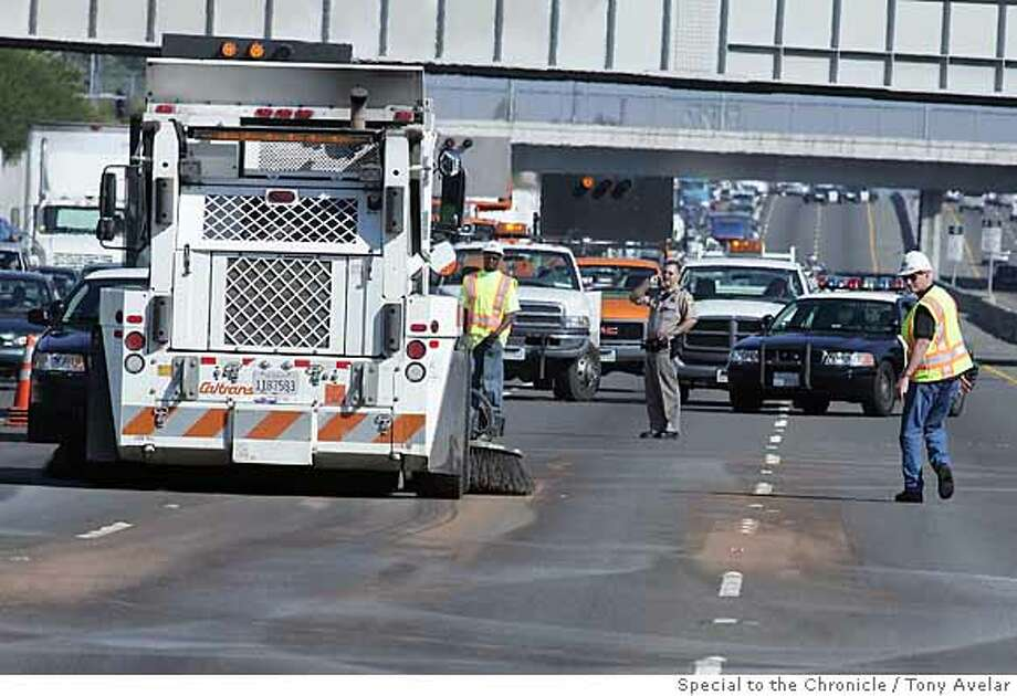 Caltrans workers clean up the brownish milk by-product that was previously thought to be raw sewage which closed southbound Highway 880 at Thornton Avenue in Fremont yesterday morning. by Tony Avelar/SPECIAL TO THE CHRONICLE Photo: Tony Avelar