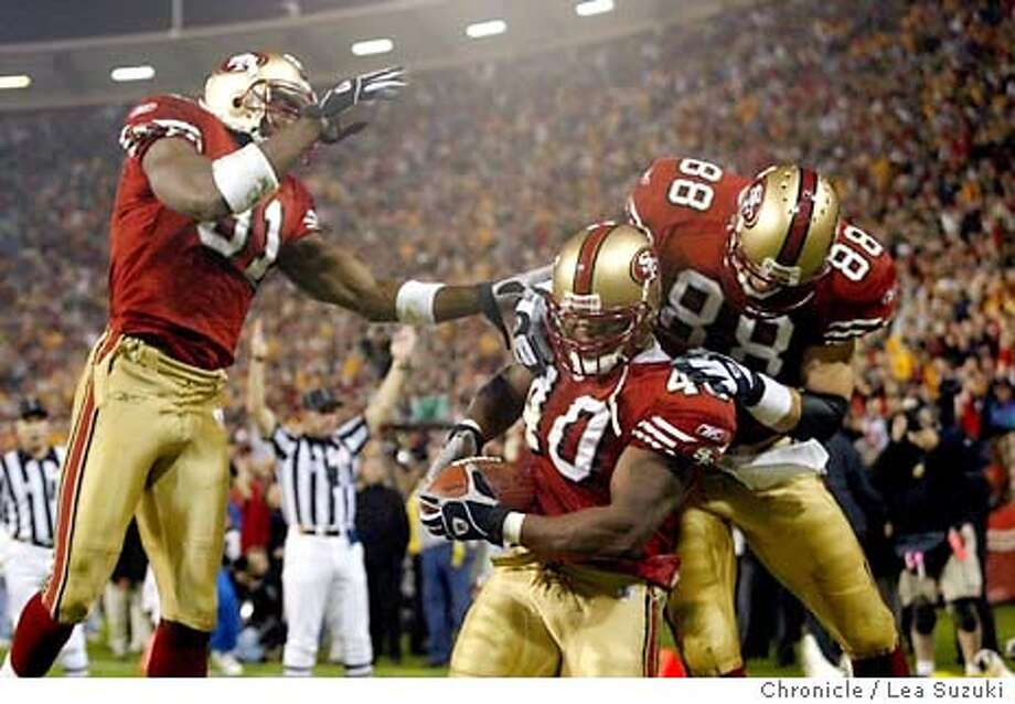 49ers's Terrell Owens, left, and Jed Weaver, top right, celebrate Fred Beasley's touchdown in the third quarter of play at Candelstick Park in San Francisco, Ca., on Monday, November 17, 2003. The 49ers played the Pittsburgh Steelers on Monday Night Football. Event on 11/17/03 in San Francisco, CA. Lea Suzuki / The San Francisco Chronicle Photo: Lea Suzuki