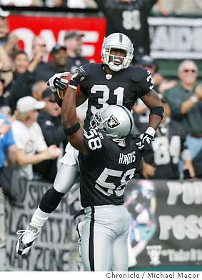 Raiders Phillip Buchanon #31 celebrates his interception for a TD with #58 Napoleon Harris in the 1st quarter.  Oakland Raiders vs Minnesota Vikings at Network Associates Coliseum.  Event on 11/16/03 in Oakland.  MICHAEL MACOR / The Chronicle Photo: MICHAEL MACOR