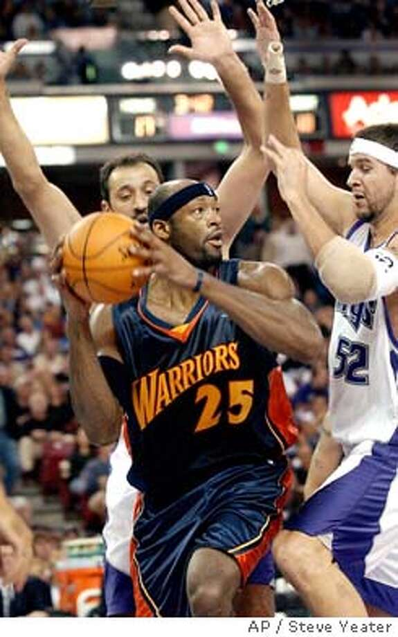 Golden State Warriors center Erick Dampier (25) pulls down a rebound in between Sacramento Kings defenders Vlade Divac of Serbia-Montenegro, left, and Brad Miller, right, during the first half in Sacramento, Calif., on Sunday, Nov. 16, 2003.(AP Photo/Steve Yeater) Photo: STEVE YEATER