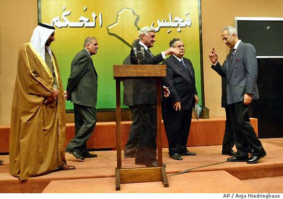 "Members of the Iraqi Governing Council with Iraqi Council President Jalal Talabani, center right, arrive for a press conference in Baghdad, Saturday, Nov 15, 2003. The U.S.-led occupation will end by June after selection of transitional government, the Iraqi Governing Council said Saturday. After that, the U.S. military status would change from an occupation force to a ""military presence,"" the council president said. (AP Photo/Anja Niedringhaus) Photo: ANJA NIEDRINGHAUS"