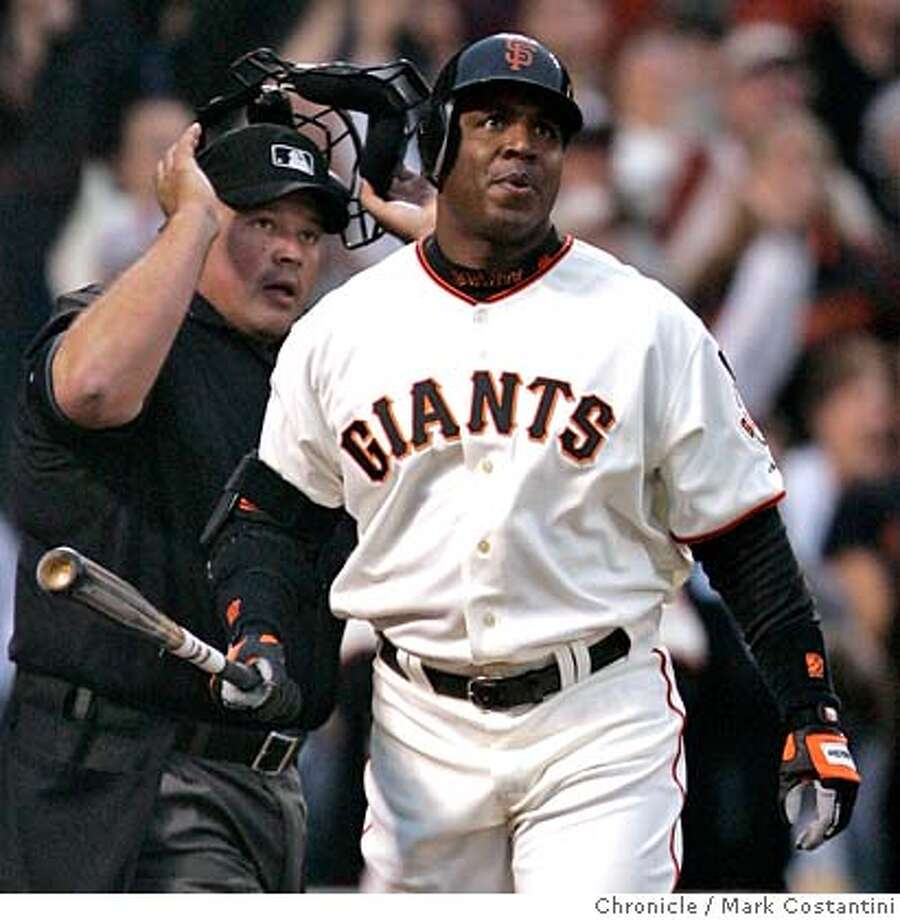Barry Bonds and Home plate umpire Wally Bell (left)watch the ball fly over the home run fence after Bonds hits home run 757.  Giants v. Nationals at ATT Park.  Photo: Mark Costantini / S.F. Chronicle Photo: Mark Costantini