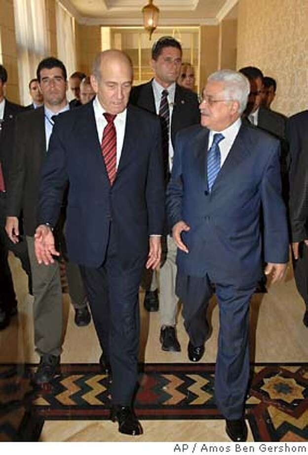 In this photo released by Israel's Government Press Office, Israel's Prime Minister Ehud Olmert, left, walks with Palestinian Authority President Mahmoud Abbas, right, as he arrives for a meeting at a hotel in the West Bank town of Jericho, Monday, Aug. 6, 2007. Olmert on Monday will become the first Israeli prime minister to visit a Palestinian city since the outbreak of fighting seven years ago, meeting Abbas in Jericho to discuss the creation of a Palestinian state. (AP Photo/Amos Ben Gershom,GPO,HO) ** ISRAEL OUT ** PHOTO RELEASED BY ISRAEL'S GOVERNMENT PRESS OFFICE - ISRAEL OUT Photo: AMOS BEN GERSHOM