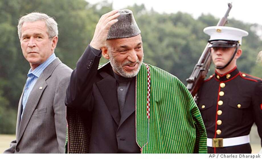 ** RETRANSMISSION FOR ALTERNATE CROP ** President Bush, left, walks with Afghanistan's President Hamid Karzai at Camp David, Md., Sunday, Aug. 5, 2007. (AP Photo/Charles Dharapak) Photo: Charles Dharapak