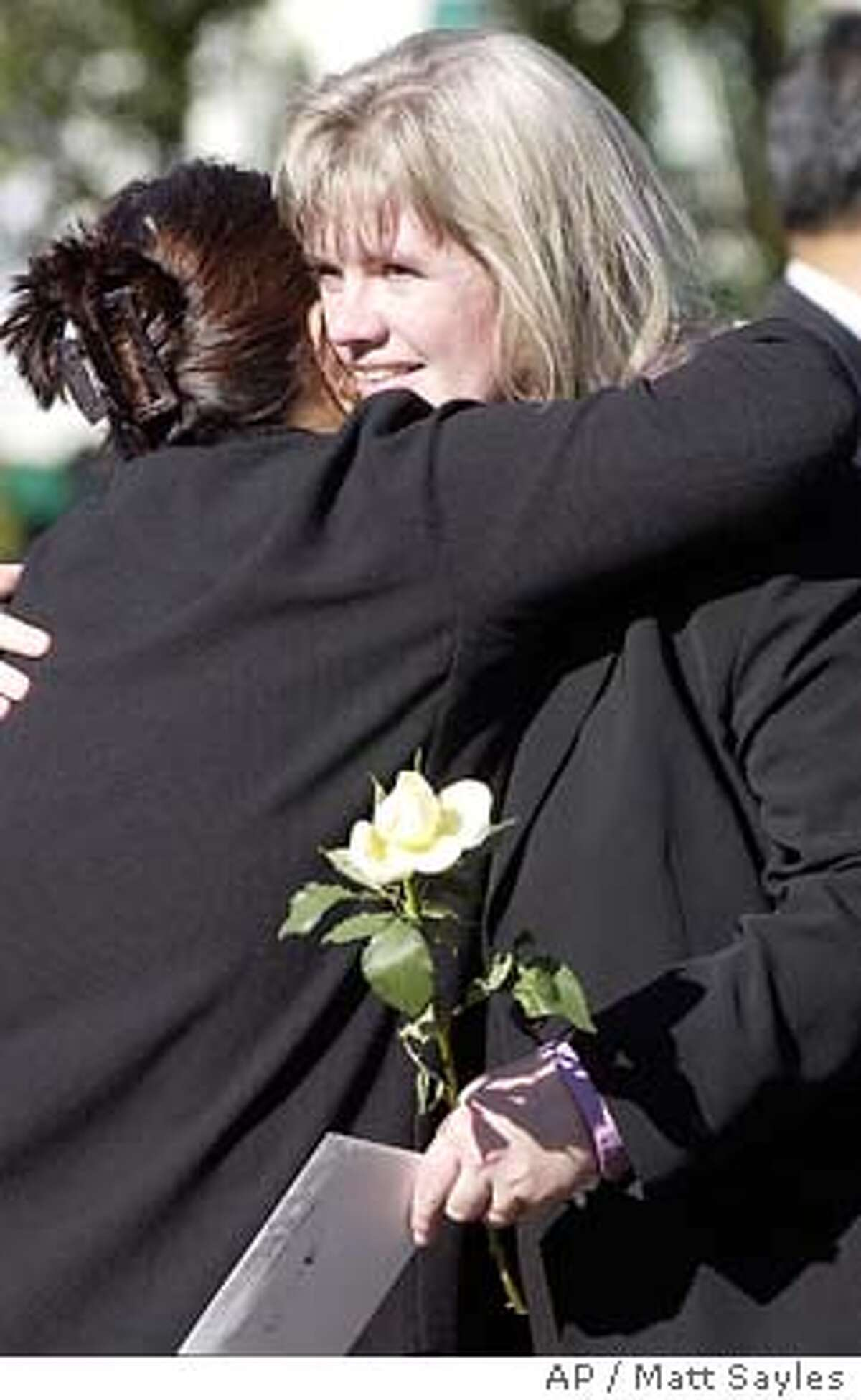 Cathy Rucker, facing camera, gets a hug from an unidentified person after a memorial service for her husband, fallen firefighter Steven Rucker, in San Rafael, Calif., Wednesday, Nov. 12, 2003. Steven Rucker died Oct. 29 battling one of the fires that ravaged Southern California. (AP Photo/Matt Sayles)