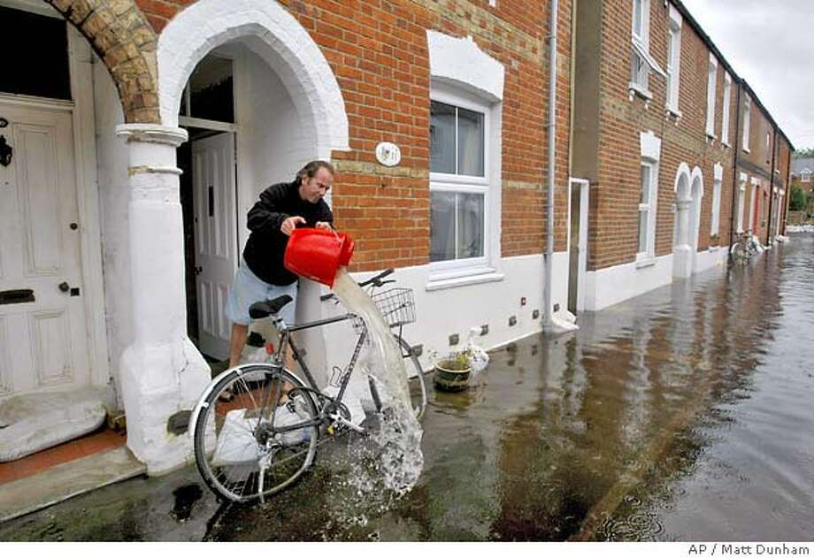 � Bill Lynch, originally from San Francisco, USA, bails water out from his mother-in-law's house in Oxford, England, Thursday July 26, 2007. River levels stabilized across England on Thursday, allowing residents of flood-ravaged areas to survey the damage and begin the clean-up, but hundreds of thousands of people remain without clean running water in the hardest-hit region. (AP Photo/Matt Dunham) Photo: MATT DUNHAM