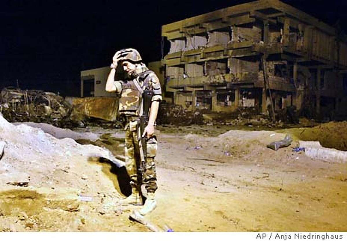 An Italian Army soldier gesture next to the barracks building which was destroyed by a car bomb, at the headquarters of Italy's paramilitary police in Nasiriyah, Wednesday, Nov. 12, 2003. At least 17 Italian soldiers and eight Iraqi civilians died. (AP Photo/Anja Niedringhaus)