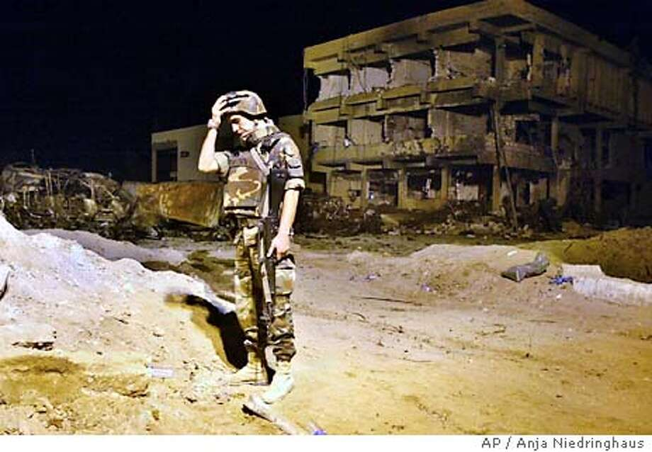 An Italian Army soldier gesture next to the barracks building which was destroyed by a car bomb, at the headquarters of Italy's paramilitary police in Nasiriyah, Wednesday, Nov. 12, 2003. At least 17 Italian soldiers and eight Iraqi civilians died. (AP Photo/Anja Niedringhaus) Photo: ANJA NIEDRINGHAUS