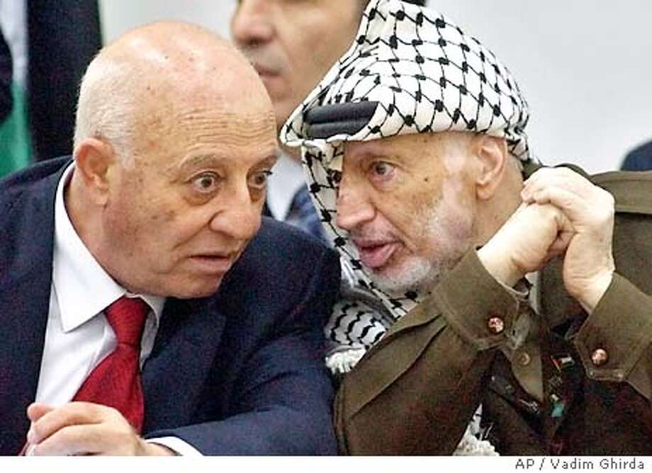 Palestinian leader Yasser Arafat, right, speaks to Palestinian Prime Minister Ahmed Qureia, left, during a parliament session in Ramallah Wednesday, Nov. 12, 2003. Qureia called for an immediate and comprehensive ceasefire with Israel and a return to peace talks based on President Bush's vision for two states. Qureia issued the call at a parliament session at which he was expected to win approval for his new cabinet. (AP Photo/Vadim Ghirda) Photo: VADIM GHIRDA