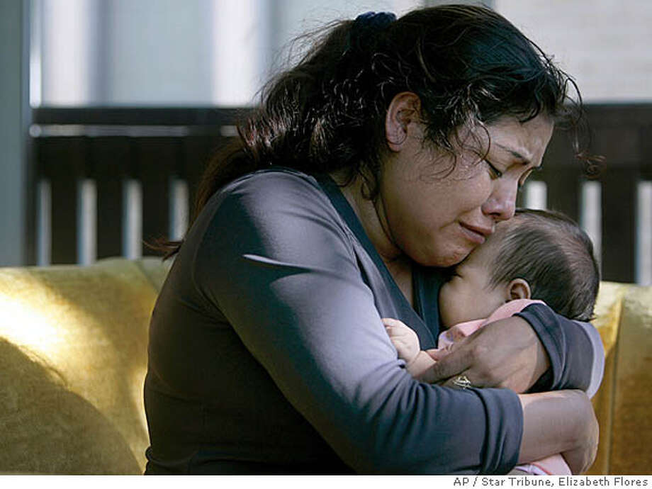 Abundia Martinez, 31, weeps as she hugs her 2-month-old daughter, Lorena Trinidad Martinez, at their home after speaking to her family in Mexico to give news of her husband, Artemio Trinidad-Mena, 29, who was killed in Wednesday's bridge collapse, according to the Hennepin County Medical Examiner's Office. Trinidad-Mena also has three young children in Mexico. (AP Photo/Star Tribune, Elizabeth Flores) ** ST. PAUL OUT TV OUT MAGS OUT NO SALES ** Photo: Elizabeth Flores