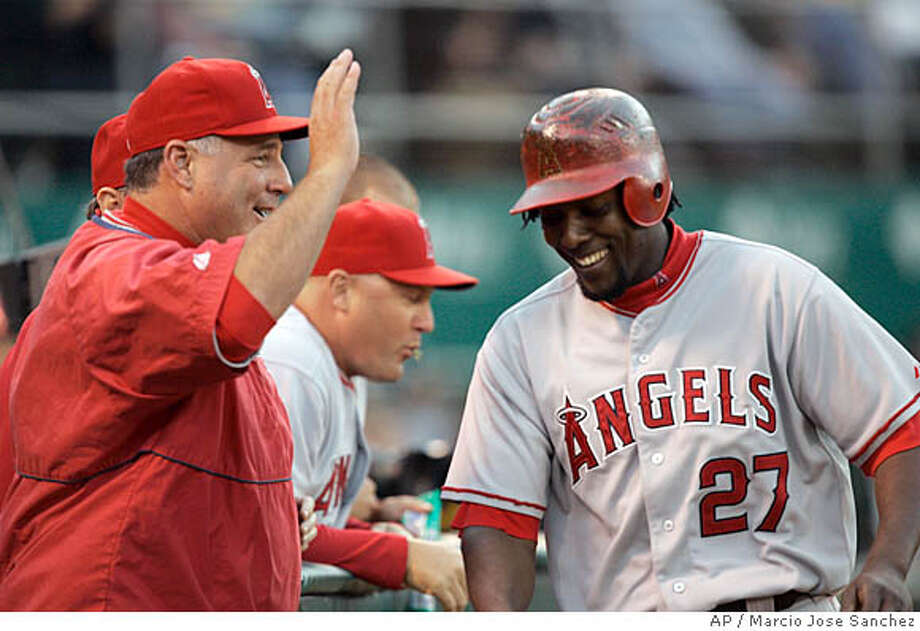 Los Angeles Angels manager Mike Scioscia, left, congratulates Vladimir Guerrero after Guerrero's home run off Oakland Athletics pitcher Chad Gaudin in the fourth inning of a baseball game in Oakland, Calif., Thursday, Aug. 2, 2007.(AP Photo/Marcio Jose Sanchez) Photo: Marcio Jose Sanchez
