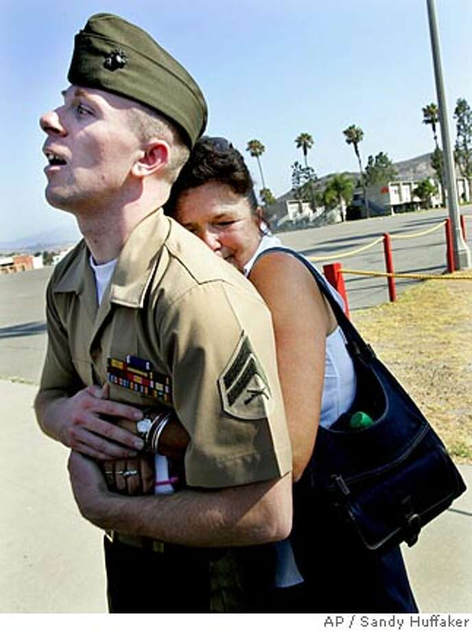 Marine Cpl. Marshall Magincalda, 24, is embraced by his stepmother Leanne Magincalda after Jury deliberations on Friday, Aug. 3, 2007, at Camp Pendlleton, Calif. A jury sentenced Magincalda Friday to time served and reduced his rank to private for conspiring to murder an Iraqi civilian during a frustrated search for an insurgent. (AP Photo/Sandy Huffaker) Photo: Sandy Huffaker