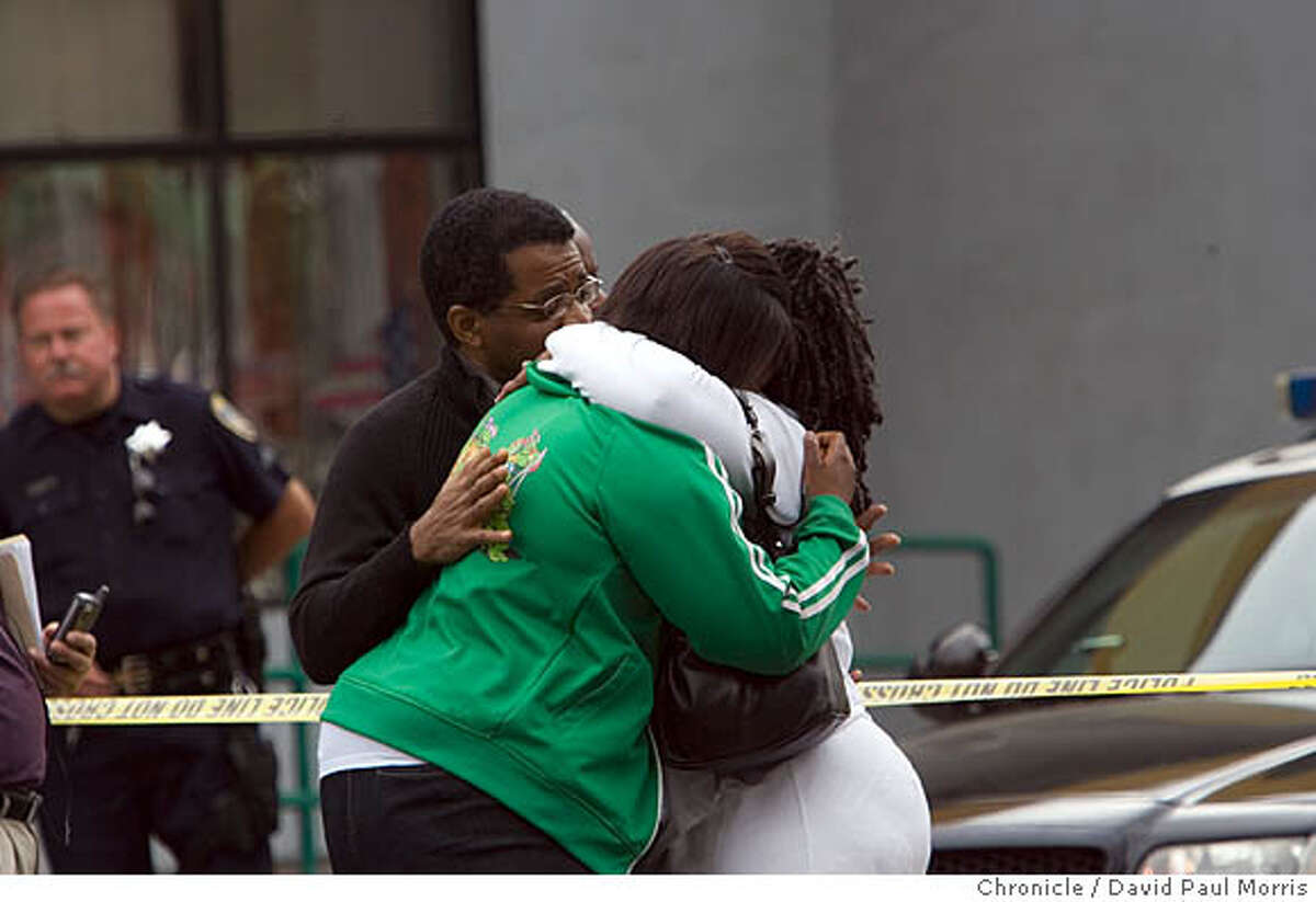 OAKLAND, CA - AUG 2: Gwendolyn Carter (C) and John Bowans (L) both co-workers with Chauncey Bailey grieve as police investigate the homicide of Chauncey Bailey, 58 on August 2, 2007 in Oakland, California. Bailey, the editor of the Oakland Post, was gunned down on 14th street in downtown Oakland in the early morning hours as he was walking to work. (Photo by David Paul Morris / The Chronicle)