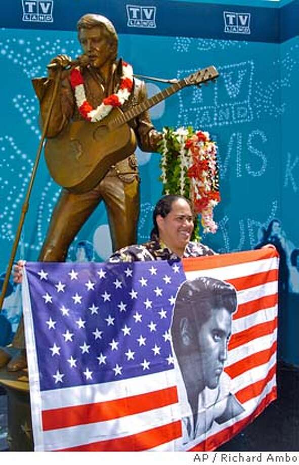 "Victoria Lum poses with an Elvis flag in front of the newly unveiled statue of Elvis Presley, Thursday, July 26, 2007, in Honolulu. Elvis is back in Hawaii. A life-sized Elvis Presley statue was unveiled today at the Neal Blaisdell Center, the site of his legendary ""Aloha from Hawaii"" concert. It coincides with tributes to commemorate the 30th anniversary of Presley's death at Graceland on August 16th, 1977. (AP Photo/The Honolulu Advertiser, Richard Ambo) ** HONOLULU OUT ** Photo: Richard Ambo"