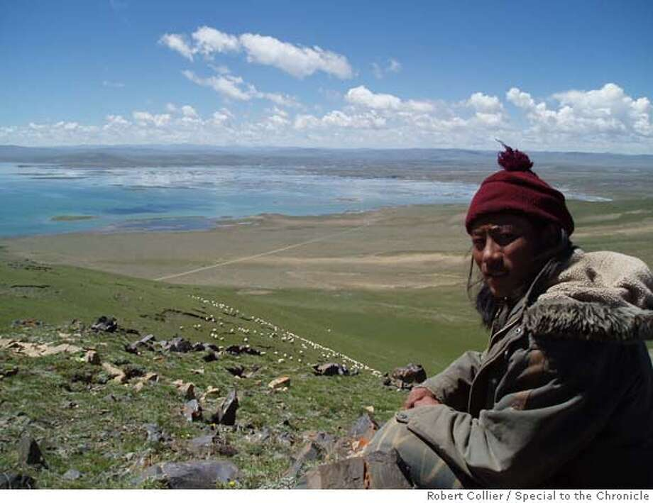 china_warming01_ph001.jpg Namgyal Tsering, a 22-year-old nomadic shepherd, watched his flock of sheep above the wetlands around Gyaring Lake. At 14,000' elevation, the lake forms the source of the Yellow River, which is China's second-longest river and which waters the dry northern grainbelt. Tsering said the poor rains of recent years has made it harder to make a living from his sheep (down the hill, in background) and yaks. Robert Collier / The Chronicle  Ran on: 08-01-2007  Namgyal Tsering, 22, a nomadic shepherd, watches his sheep above the wetlands around Gyaring Lake. At 14,000 feet elevation, it is the source of the Yellow River, China's second longest. Photo: Robert Collier