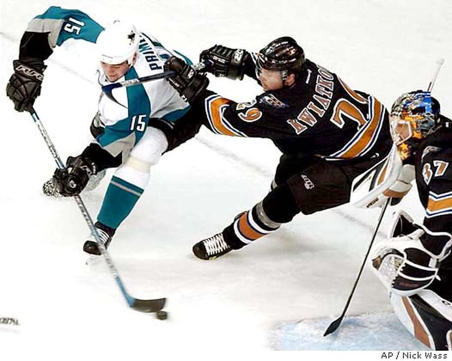 San Jose Sharks' Wayne Primeau (15) tries to get around Washington Capitals' Joel Kwiatkowski (29) and goalie Olaf Kolzig, right, of South Africa, during the first period Saturday, Nov. 8, 2003, in Washington. (AP Photo/Nick Wass) Photo: NICK WASS
