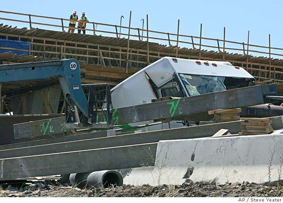 A FedEx truck lies beneath iron support beams that fell when a bridge that was under construction collapsed near Oroville, Calif., on Tuesday, July 31, 2007. Firefighters swarmed the FedEx delivery truck to cut its driver from underneath a large steel beam that crushed the hood but missed the cab. A second beam landed on the back of the truck. The cause of the collapse was being investigated. (AP Photo/Steve Yeater) Photo: Steve Yeater