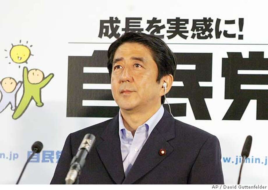 Japanese Prime Minister Shinzo Abe, left, and Liberal Democratic Party Secretary-General Hidenao Nakagawa react after learning the return of the upper house elections at the party headquarters in Tokyo Sunday, July 29, 2007. Projections indicated the LDP would fall far short of the 64 seats it needs to maintain a majority in the upper chamber, allowing the main opposition Democratic Party of Japan to greatly boost its standing. (AP Photo/David Guttenfelder) Photo: DAVID GUTTENFELDER