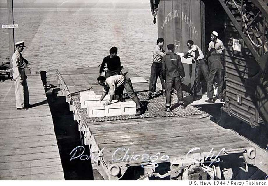 In this 1943 photo taken by a U.S. Navy photographer, and released by Percy Robinson in Los Angeles on Friday, July 20, 2007; Robinson, then 18 and a U.S. Navy Seaman First Class, is seen bending to load ammunition into a cargo net to be loaded aboard a ship in Port Chicago, Calif. During World War II some African-American sailors were working in a munitions factory in Port Chicago, Calif., under what they believed to be dangerous conditions. After an explosion at the site, some members of a work crew went on strike and were charged with mutiny. Sailor Percy worked there, and was involved in the work stoppage, but was not charged with mutiny. He received a summary court marshal, and was later charged with disobeying orders. (AP Photo/Percy Robinson) RELEASED BY PERCY ROBINSON IN LOS ANGELES FRIDAY, JULY 20, 2007 Photo: U.S. Navy Photo Via Percy Robins
