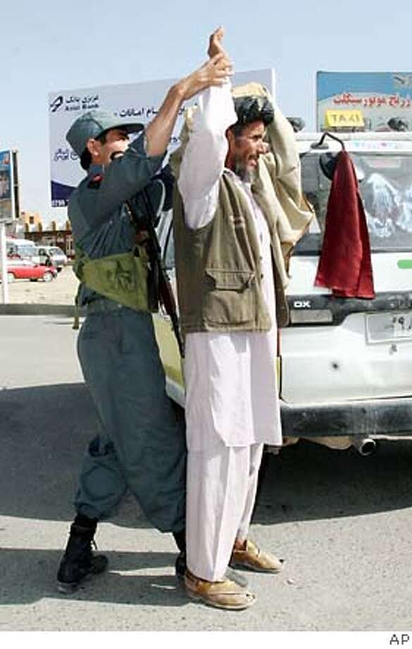 An Afghan officer frisks a man at a checkpoint in Ghazni province, where a group of South Koreans was kidnapped. Associated Press photo