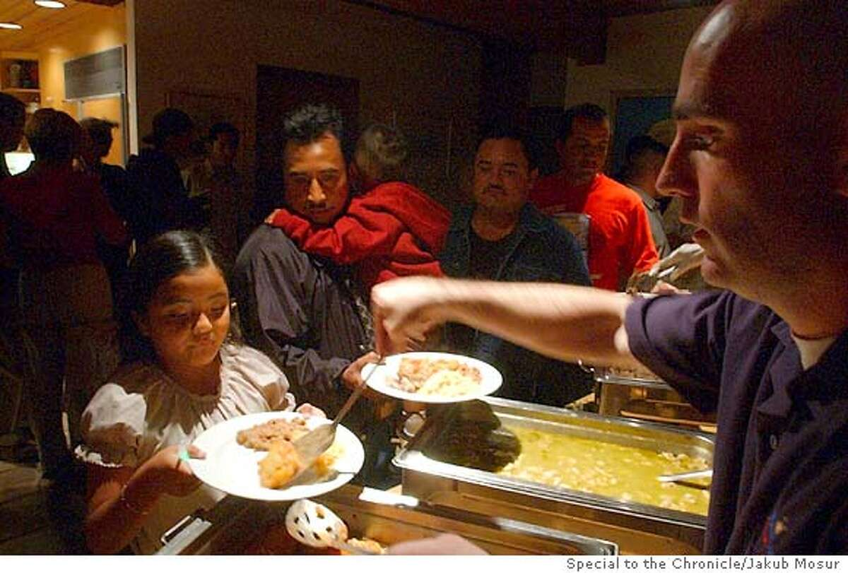 Dan Lacau, of Villa Corona Catering, serves up a chile rellnos for Marlenne Villanueva, 7, as her father waits for his portion during a crush and harvest celebration party for Frog's Leap winery held at Frank Leeds home in Rutherford on Friday Oct. 17, 2003. Event on 10/17/03 in Rutherford. JAKUB MOSUR / The Chronicle