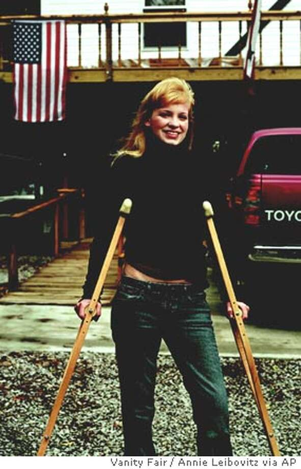 """Former POW Jessica Lynch is photographed Wednesday, Oct. 1, 2003, for Vanity Fair's 2003 Hall of Fame, which appears in the December issue, with her parents Greg and Deadra, outside their home in Palestine, W.Va. Lynch is still recovering from injuries she sustained while serving in Iraq. Reports released Thursday say Lynch reveals in her book, """"I am a Soldier, Too: The Jessica Lynch Story,"""" that she was raped by her Iraqi captors. The book is scheduled to be released Tuesday, Nov. 11, 2003. (AP Photo/Vanity Fair, Annie Leibovitz, HO) ONE TIME USE ONLY. THIS PHOTO MAY NOT BE CROPPED. , NO ARCHIVE, NO MAGS Photo: ANNIE LEIBOVITZ"""