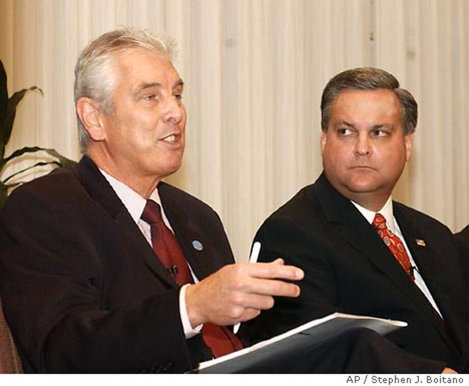 Peter Nevitt, director of Information Systems at Interpol, left, accompanied by Bruce Townsend, deputy assistant director of Investigation of the U.S. Secret Service, gestures during a news conference at the National Press Club in Washington Wednesday, Nov. 5, 2003 where it was announced that Microsoft Corp. is creating a $5 million reward program to help law enforcement identify and convict those who illegally release worms, viruses and other types of malicious programs on the Internet. (AP Photo/Stephen J.Boitano) Photo: STEPHEN J. BOITANO