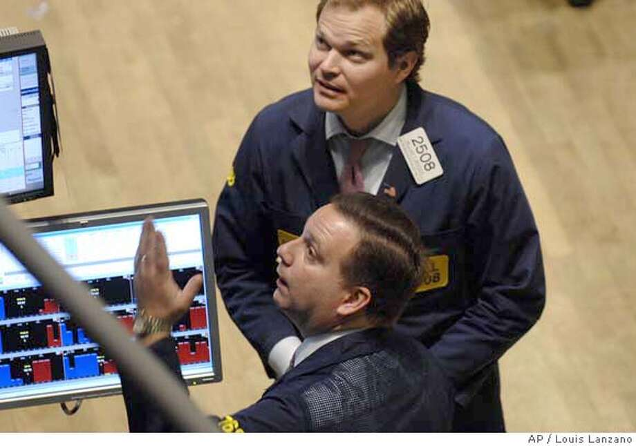 Traders confer at their post on the floor of the New York Stock Exchange, Friday, July 27, 2007, in New York. Wall Street extended its steep decline Friday, propelling the Dow Jones industrials down more than 500 points over two days after investors gave in to mounting concerns that borrowing costs would climb for both companies and homeowners. It was the Dow's worst week in nearly five years. (AP Photo/ Louis Lanzano) Photo: LOUIS LANZANO