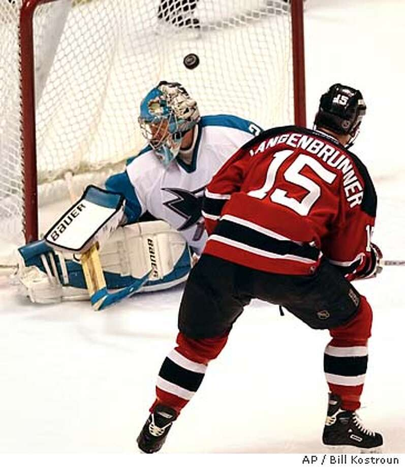 New Jersey Devils' Jamie Langenbrunner (15) scores the winning goal against San Jose Sharks goaltender Evgeni Nabokov, of Kazakstan, to give the Devils a 3-2 win in overtime Wednesday night, Nov. 5, 2003, in East Rutherford, N.J. (AP Photo/Bill Kostroun) Photo: BILL KOSTROUN
