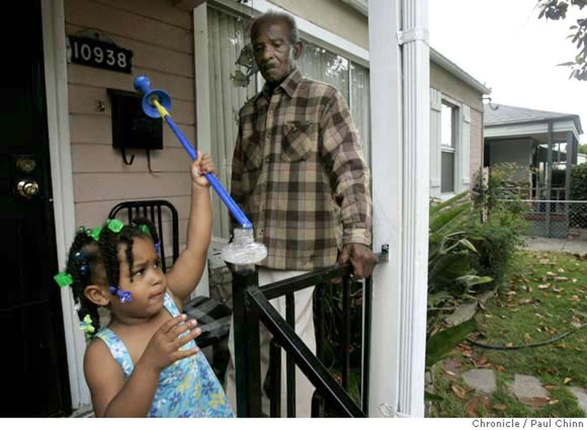 Johnnie Gardner watches his great niece Maaiah Bias play with a bubble wand on the front porch of his home in Oakland, Calif. on Tuesday, July 3, 2007. The Gardners face foreclosure on their home of 53 years after refinancing several times with a $4,000-a-month mortgage. JoAnn Gardner had to leave her job to care full-time for her elderly parents Johnnie and Estelle Gardner and can't afford to keep up with the payments. PAUL CHINN/The Chronicle **JoAnn Gardner, Johnnie Gardner, Estelle Gardner, Maaiah Bias MANDATORY CREDIT FOR PHOTOGRAPHER AND S.F. CHRONICLE/NO SALES - MAGS OUT
