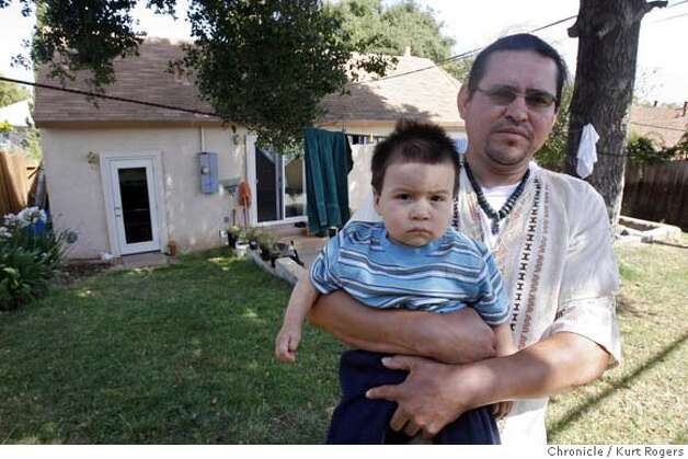 Carlos Cil and his one year old son Brandon in the back yard of his Vallejo home. He started out with a mortgage that reset at a higher interest rate and had to get a second job to afford the payments. He found a community group that is going to refi his mortgage at a lower rate. TUESDAY, JULY 24, 2007 KURT ROGERS VALLEJO SFC  THE CHRONICLE FORECLOSExx_0040_kr.jpg MANDATORY CREDIT FOR PHOTOG AND SF CHRONICLE / NO SALES-MAGS OUT Photo: KURT ROGERS