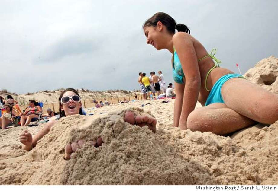Michelle Clark, 13, is buried in the sand by her friend Annie Chamoun, 14, at Cape Henlopen State Park in Delaware. Probably thousands of microscopic creatures are in the pile covering her legs, a microscopic world that has begun to be explored only in the last 100 years or so. Illustrates SAND (category a), by David A. Fahrenthold � 2007, The Washington Post. Moved Tuesday, July 10, 2007. (MUST CREDIT: Washington Post photo by Sarah L. Voisin.)  Ran on: 07-29-2007  Michelle Clark, 13, is buried by Annie Chamoun, 14, at Cape Henlopen State Park in Delaware. Thousands of microscopic creatures are in the pile covering her legs. Photo: VOISIN