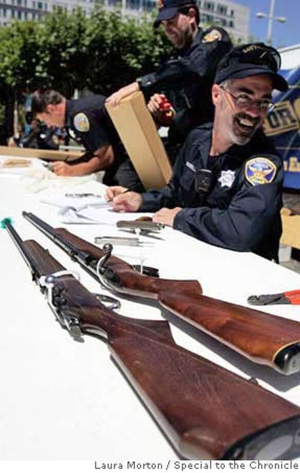 "giftsforguns_0022_LKM.jpg San Francisco police officers, including Len Broberg (left) collect guns at Civic Center Plaza on Saturday afternoon as part of an exchange program called ""Gifts for Guns."" People who chose to turn in their guns were rewarded with gift cards. The officers said that over 90 guns were collected. (Laura Morton/Special to the Chronicle) *** Len Broberg Photo: Laura Morton"