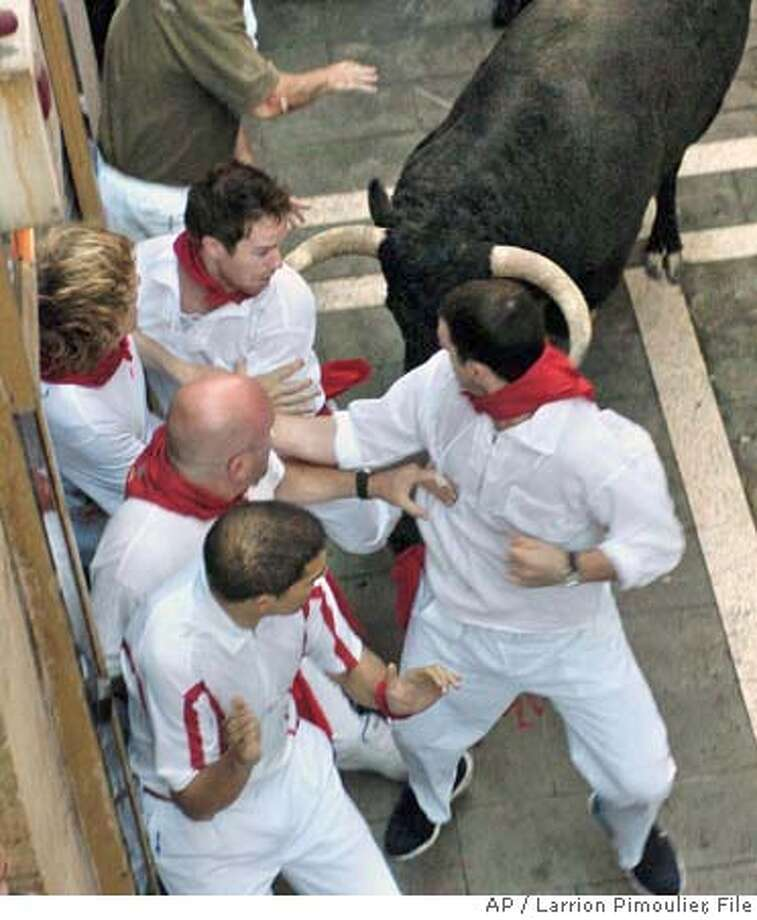 ** CORRECTS SPELLING TO LAWRENCE ** U.S. brothers Lawrence, left, and Michael Lenahan are seen an instant before being gored at the same time by a fighting bull during a traditional bull run in Pamplona, Spain, Thursday July 12, 2007. The two brothers were gored Thursday during the longest and bloodiest morning bull run at the San Fermin festival in the northeastern city of Pamplona. Lawrence Lenahan, 26, of Hermosa Beach, Calif. and Michael Lenahan, 23, of Philadelphia, Pa. were gored by a bull who strayed from the pack, turned around and ran the wrong way. (AP Photo/ Larrion Pimoulier) EFE OUT, PHOTO MADE AVAILABLE FRIDAY JULY 13, 2007 CORRECTS SPELLING TO LAWRENCE Photo: LARRION PIMOULIER