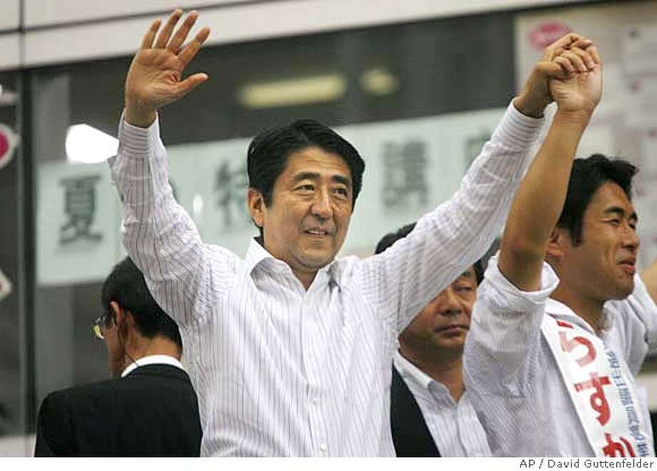 Japanese Prime Minister Shinzo Abe waves to supporters outside a train station in Matsudo, Japan on Thursday, July 26, 2007 as he campaigns for his party's candidates ahead of parliamentary elections this coming weekend. (AP Photo/David Guttenfelder) Photo: DAVID GUTTENFELDER