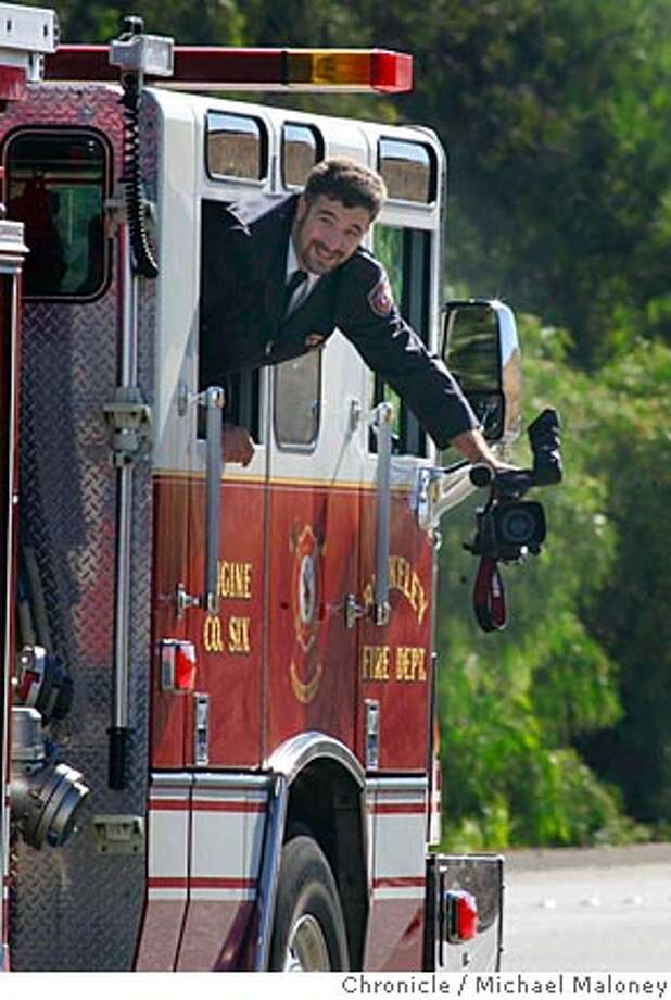 A Berkeley Firefighter video tapes the fire trucks behind during the procession.  A miles long memorial procession of fire trucks from throughout the state wound their way from the Sun Valley Mall in Concord, to the Sleep Train Concord Pavilion in Concord.  Contra Costa County Fire Protection District Capt. Matt Burton, 34, and Engineer Scott Desmond, 37, are the first Contra Costa County firefighters to die in a fire in at least three decades. Both were honored at a memorial with full honors on Friday, July 27, 2007 at the Sleep Train Concord Pavilion in Concord.  Photo taken on 7/27/07 in Concord, CA  Photo by Michael Maloney / San Francisco Chronicle Photo: Michael Maloney