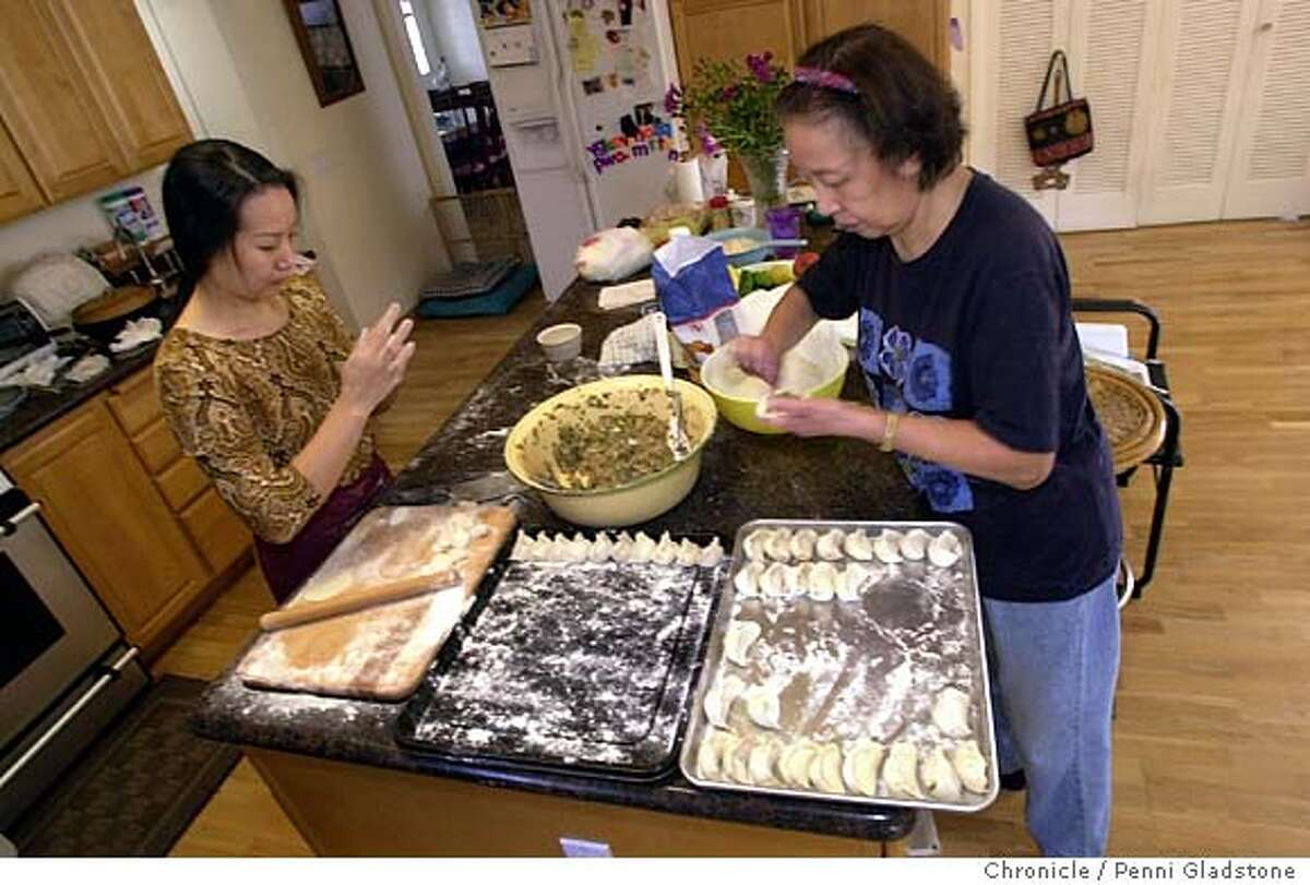Chunrong Cui and Kweichin Chu at rt making potstickers from scratch at a home in Mtn View. 10/19/03 in Mountain View. PENNI GLADSTONE / The Chronicle