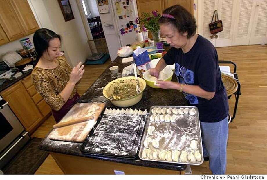 Chunrong Cui and Kweichin Chu at rt making potstickers from scratch at a home in Mtn View. 10/19/03 in Mountain View.  PENNI GLADSTONE / The Chronicle Photo: PENNI GLADSTONE