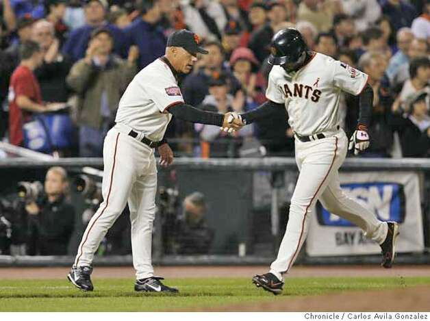 Giants third base coach Tim Flannery congratulates Pedro Feliz after Feliz hit a three-run home run in the bottom of the fifth inning.  Florida Marlins play the San Francisco Giants at AT&T Park in San Francisco, CA, on Friday, July, 27 2007. photo taken: 07/27/2007  Carlos Avila Gonzalez / The Chronicle ** (cq) Photo: Carlos Avila Gonzalez