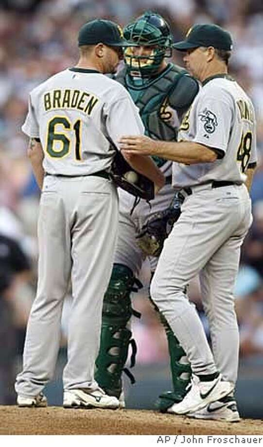 Oakland Athletics starting pitcher Dallas Braden has a talk on the mound with pitching coach Curt Young, right, and catcher Rob Bowen after giving up three runs to the Seattle Mariners during the third inning of a baseball game in Seattle on Friday, July 27, 2007. (AP Photo/John Froschauer) Photo: John Froschauer