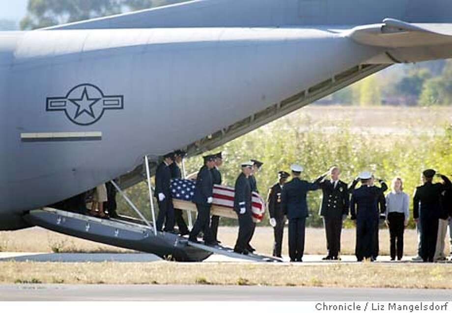 rucker043_LM.jpg Event on 11/3/03 in santa rosa. The casket containing the body of Novato Firefighter Steve Rucker is unloaded at the Santa Rosa Charles Schultz Memorial Airport as Novato firefighters and family members look on. The body was unloaded and driven in a procession down Airport blvd toward the freeway, on it's way to Novato.  LIZ MANGELSDORF / The Chronicle Photo: LIZ MANGELSDORF