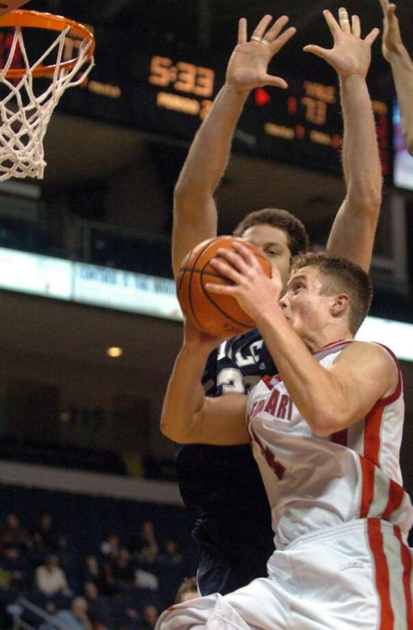 Sacred Heart's Corey Hassan goes up for a shot as Yale's Paul Nelson defends during the second half of Friday night's Connecticut 6 classic game  at the Arena at Harbor Yard. Photo: Autumn Driscoll / Connecticut Post
