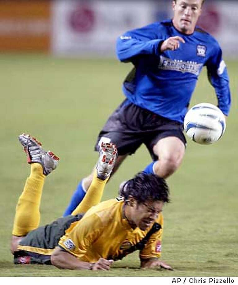 Los Angeles Galaxy's Carlos Ruiz, left, falls to the turf as he pursues the ball as San Jose Earthquakes' Richard Mulrooney follows during the first half at Home Depot Center in Carson, Calif., Saturday, Nov. 1, 2003. (AP Photo/Chris Pizzello) Photo: CHRIS PIZZELLO