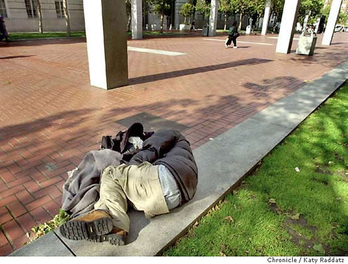 PHOTO BY KATY RADDATZ--THE CHRONICLE Un Plaza and its design and population problems. The fountain. SHOWN: A homeless person sleeps on the curb to the grassed area while pedestrians walk by.