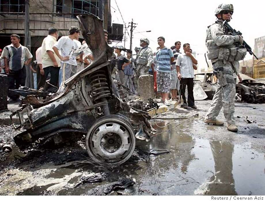 A U.S. soldier stands guard near the wreckage of a vehicle used in a car bomb attack in Baghdad July 23, 2007. At least 10 people, including two policemen, were killed and 28 wounded when two car bombs exploded almost simultaneously in different areas of Baghdad's central Karrada district, police said. Up to 20 cars were set ablaze. REUTERS/Ceerwan Aziz (IRAQ) 0 Photo: CEERWAN AZIZ