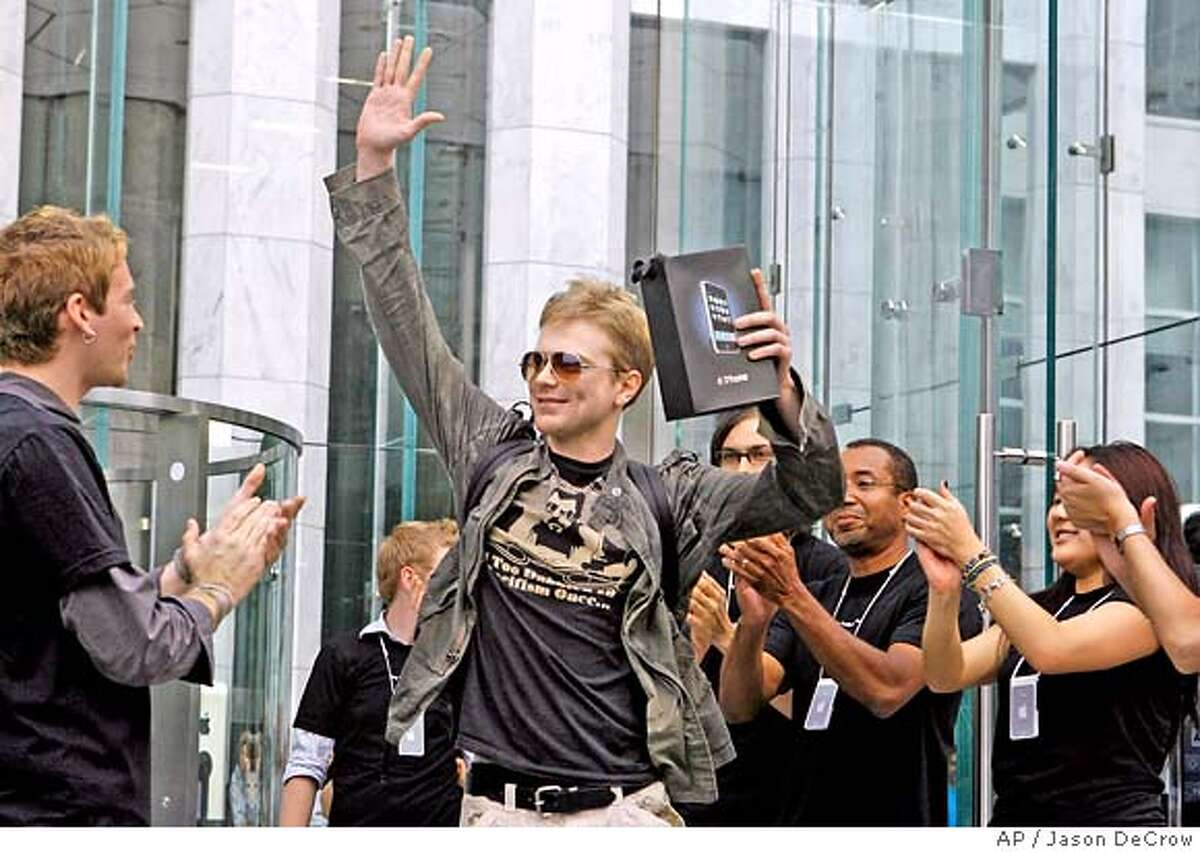 **FILE** Apple employees cheers as an excited customer leaves the Apple Store with his new iPhone in this June 29, 2007 file photo in New York. (AP Photo/Jason DeCrow, file)