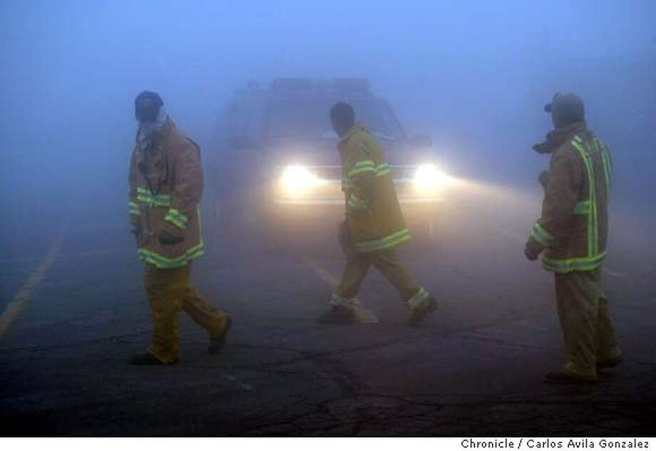 A group of firefighters walks through the heavy fog past several firetrucks at Rim of The World High School in Rimforest, Ca., on Thursday, October 30, 2003, waiting to be deployed to the front lines of the Old Fire in the San Bernardino National Forest. Firefighters found the weather had turned in their favor, with temperatures dropping and fog blanketing the region the fire had devastated the previous week. Event on 10/30/03 in Rimforest, CA. Photo By Carlos Avila Gonzalez / The San Francisco Chronicle Photo: Carlos Avila Gonzalez