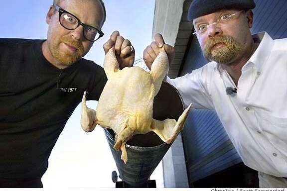 Adam Savage (left) and Jamie Hyneman (all cq), playfully display one of the chickens they are firing through their cannon (behind the chicken) to test the myth that flying birds can break through windscreens in aircraft. --- Mythbusters is this very cool new program on the Discovery Channel hosted by a Lucasfilm special effects guy named Jamie Hyneman and another fun guy named Adam Savage, who go around trying to test common myths and urban legends. Today (Friday), they're gonna build a cannon and fire a frozen chickens from it, to see if it's possible that they can break windshields.  SCOTT SOMMERDORF / The Chronicle