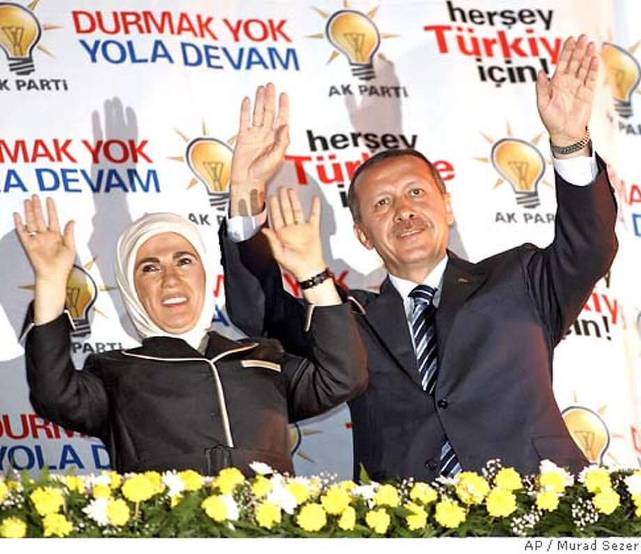Turkish Prime Minister Recep Tayyip Erdogan and his wife Emine Erdogan greet their supporters outside of the party headquarters in Ankara, Turkey, late Sunday, July 22, 2007. Turkey's Islamic-rooted ruling Justice and Development Party won parliamentary elections by a big margin Sunday in a contest that had pitted the government against opponents warning of a threat to secular traditions. (AP Photo/Murad Sezer) Photo: MURAD SEZER